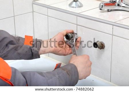 Plumber hands fixing water pipe with spanner - stock photo