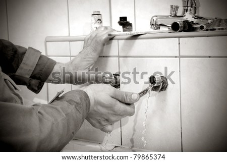 Plumber hands fixing water pipe with spanner and with leaking water from pipe - stock photo