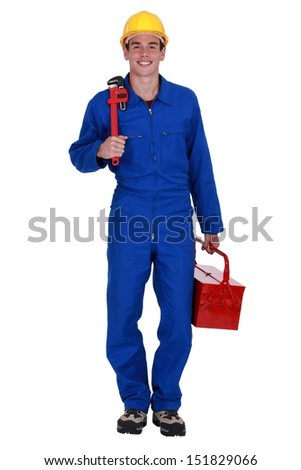 Plumber holding wrench and tool box - stock photo