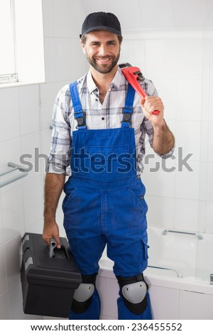 Plumber holding wrench and toolbox in the bathroom - stock photo