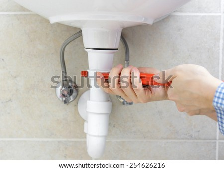 Plumber is r repairing sink In Bathroom - stock photo