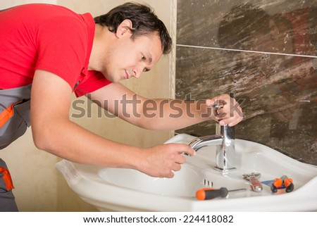 Plumber is repairing a faucet with water in the bathroom - stock photo