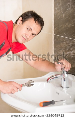 Plumber is repairing a faucet with water in the bathroom.