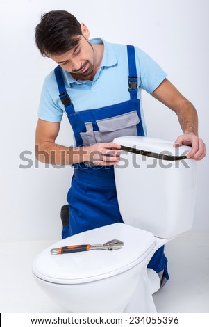 Plumber is repairing a flush toilet, on white background.