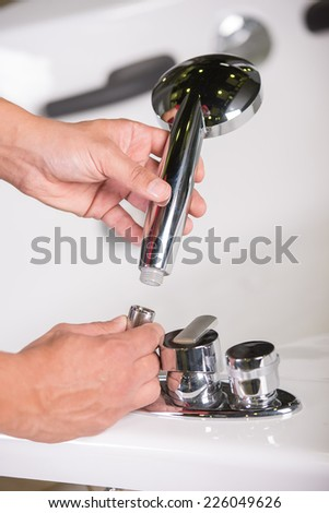 Plumber is repairing bath tub. Service. Close-up. - stock photo