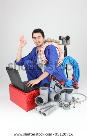 plumber kneeling with computer doing OK sign - stock photo