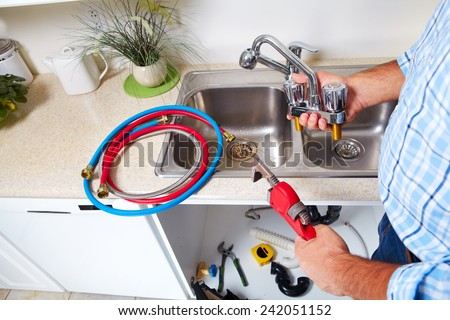 Plumber on the kitchen. Renovation  and plumbing. - stock photo