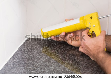 Plumber putting filling in between tiles in the kitchen - stock photo