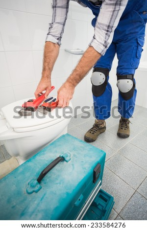 Plumber putting his tools on toilet in the bathroom - stock photo