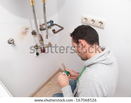 Plumber repairing an electric boiler inside home - stock photo