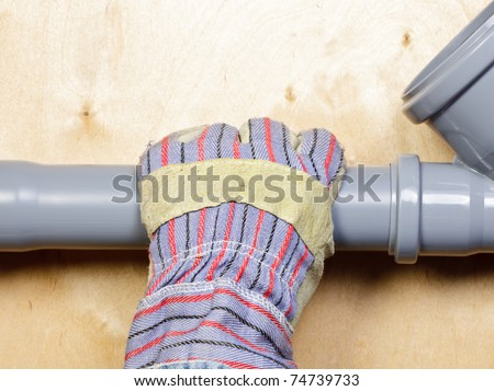 Plumber's hand wearing protective glove with pvc sewage pipes - stock photo