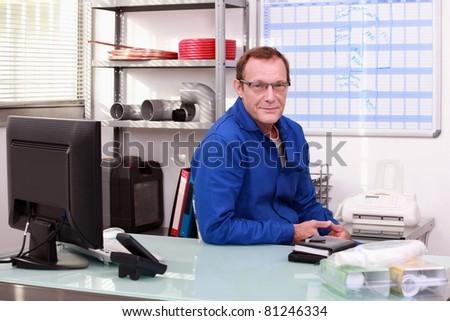Plumber sat at desk - stock photo