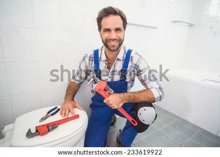Plumber smiling at the camera in the bathroom - stock photo