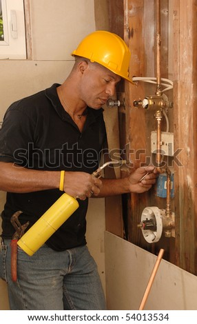 Plumber sweating a copper pipe with a propane torch - stock photo