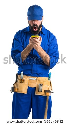 Plumber talking to mobile - stock photo