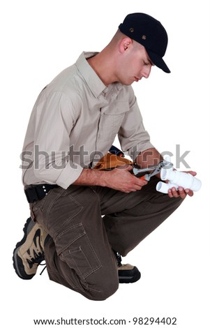 Plumber using pliers to fasten two parts together - stock photo