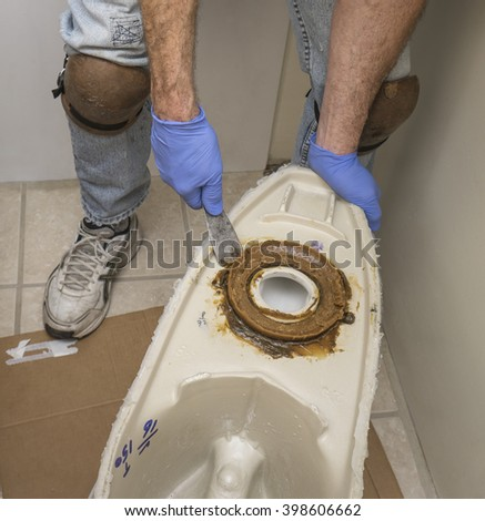 Plumber wearing knee pads installing a new toilet - stock photo