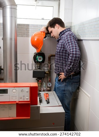 Plumber with red hard hat looking at complicated heating system
