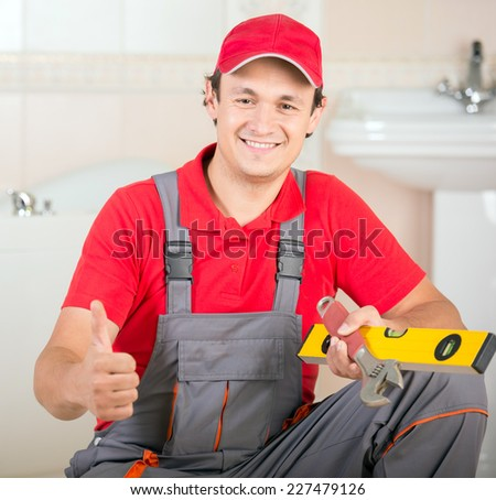 Plumber with the building level and wrench during the work. - stock photo