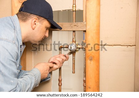 Plumber works in bathroom - stock photo