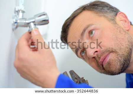 Plumbers inspecting a leak - stock photo