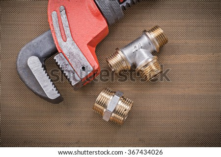 Plumbers wrench brass plumbing fixtures on cleaning mesh filter grid. - stock photo