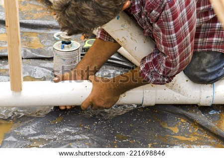 Plumbing building contractor installing plastic drain pipe in the floor section for a luxury custom house - stock photo