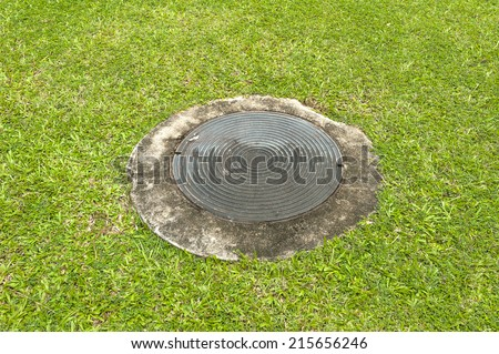 plumbing lid  cover drainage system in the midst of  grass.  - stock photo