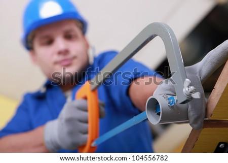 Plumbing sawing plastic pipe - stock photo