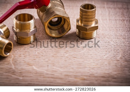 Plumbing Tools Brass Pipe Connectors On Wooden Board Close Up  - stock photo