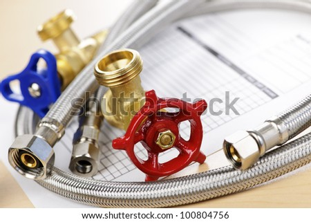 Plumbing valves hoses and assorted parts with estimate sheet - stock photo