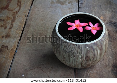 Plumeria flower floating in the ancient jug - stock photo
