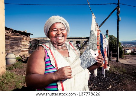 plump african woman proudly showing off her clean washing in the township - stock photo