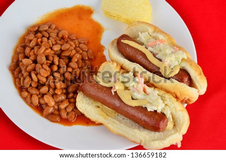 Plump juicy hot dogs on bun with coleslaw and Dijon Mustard and large helping of Pork 'n Beans.  Taken against bright red background.