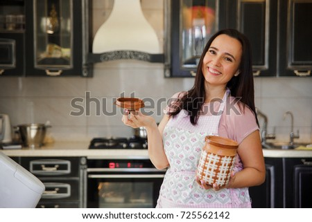 Plump woman cooking on the kitchen. Mature woman in pastel apron holding clay pot for storage and smiling.
