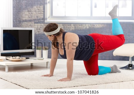 Plump woman exercising at home on floor. - stock photo