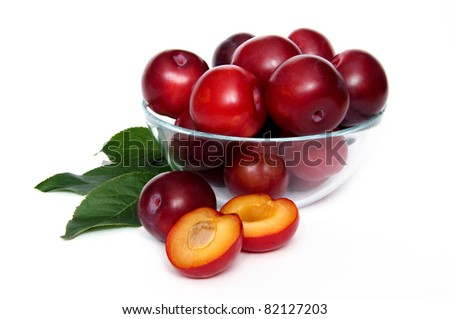 plums in a glass bowl over white background - stock photo
