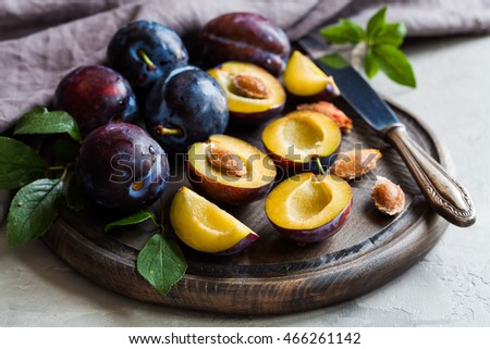 Plums, whole and slices on the wooden board
