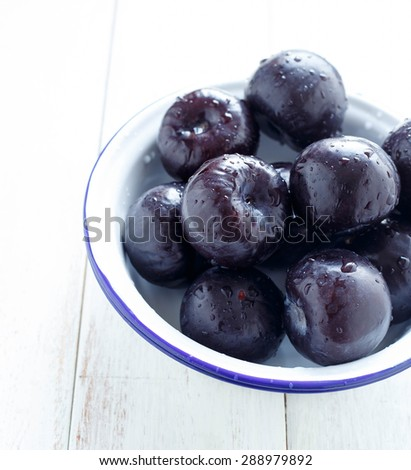 Plums Whole Plums in a blue rimmed white bowl  - stock photo