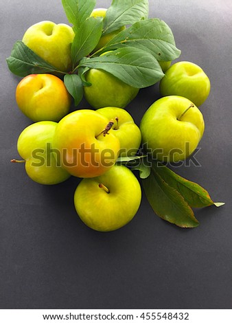 Plums with leaves on a dark background