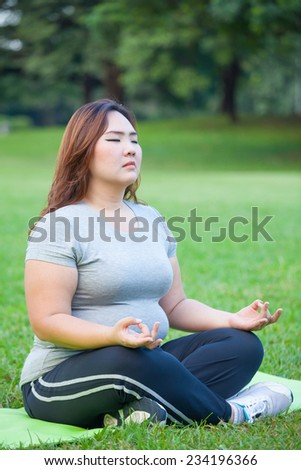 Plus size asian woman practicing yoga on green grass in the park - stock photo