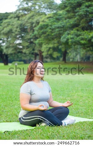 Plus size asian woman practicing yoga on green grass in the park