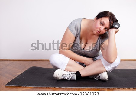 Plus size woman is fed up and tired of exercising - stock photo