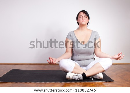 Plus size woman practicing yoga, lotus position - stock photo