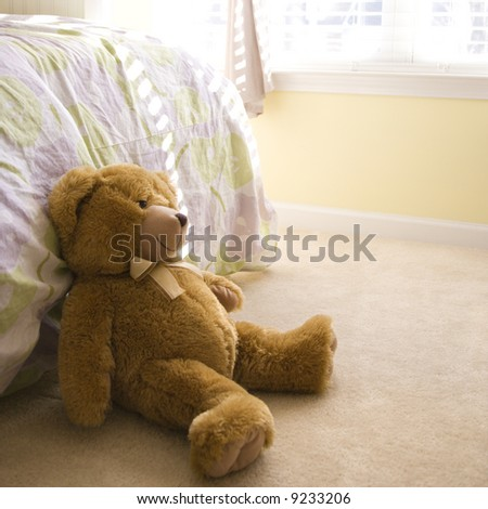 Plush brown teddy bear on bedroom floor. - stock photo
