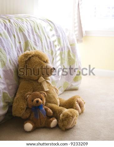 Plush brown teddy bears on bedroom floor. - stock photo