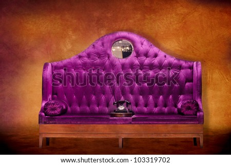Plush purple velvet loveseat settee with antique style telephone against a textured background - stock photo