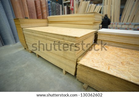 Plywood of different sizes lie on racks and pallets in build supermarket - stock photo