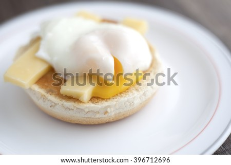 Poached egg on muffin with cheddar cheese. - stock photo