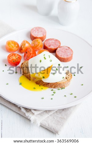 Poached egg on piece of wholegrain bread with vegetables and herbs for breakfast close up